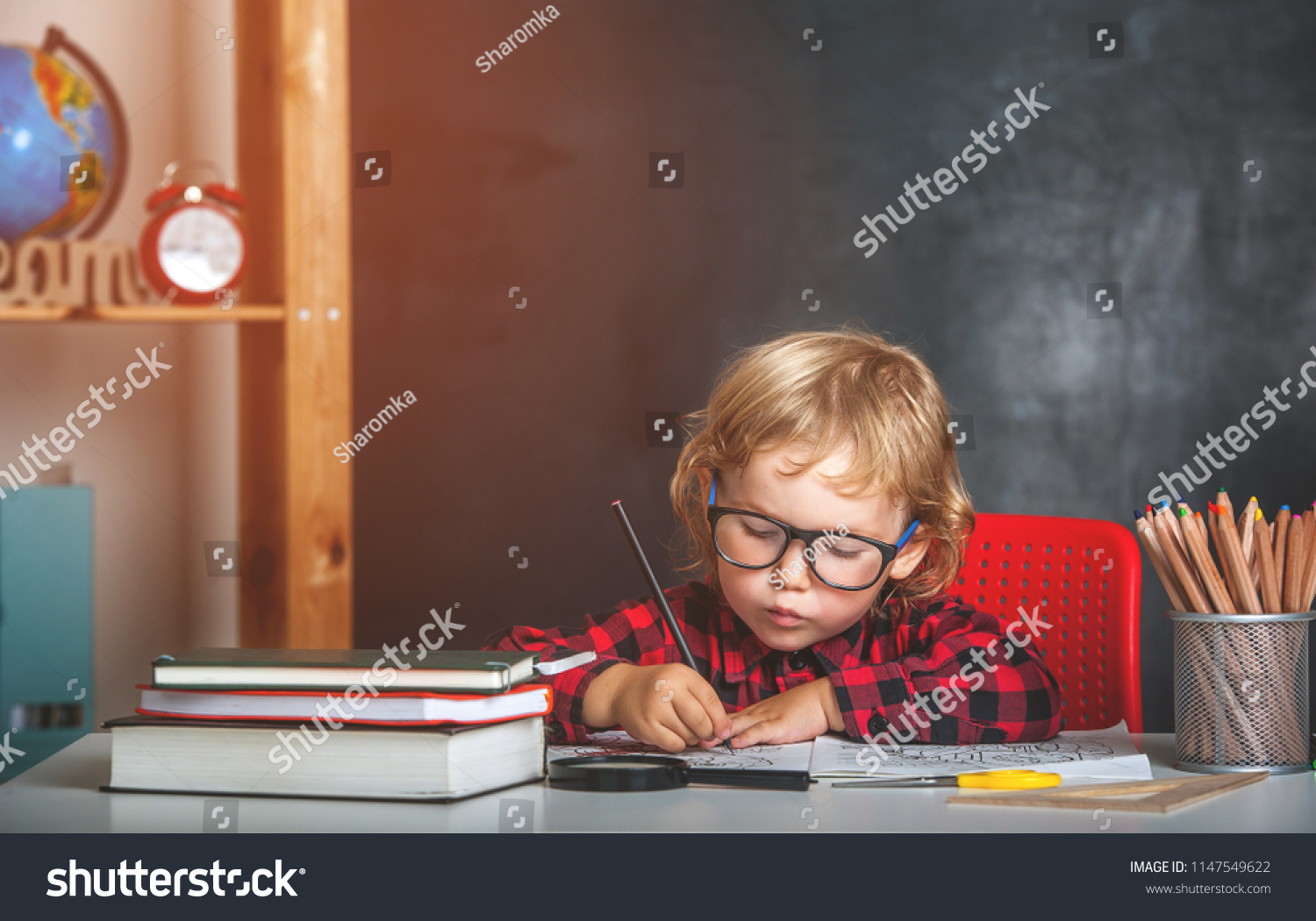 Back to school. Happy smiling pupil drawing at the desk. Child in the class room with blackboard on background. Alarm clock, pencils, books. Kid girl from primary school. first day of fall. #1147549622