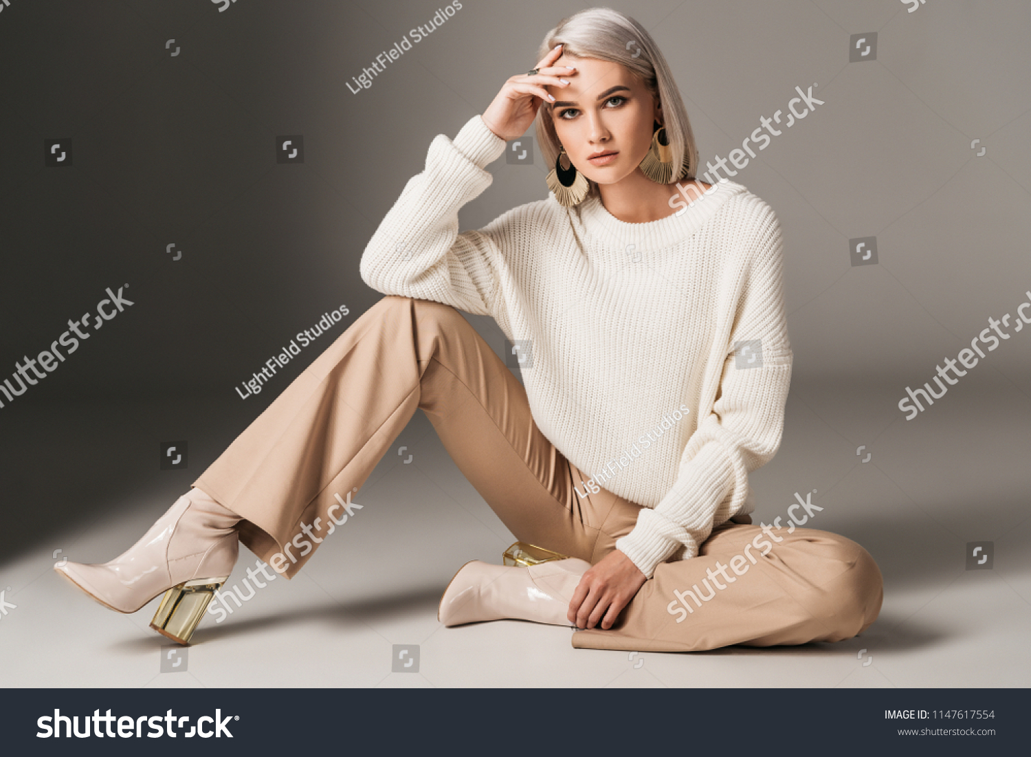 attractive fashionable woman posing in white trendy sweater, beige pants and autumn heels, on grey  #1147617554