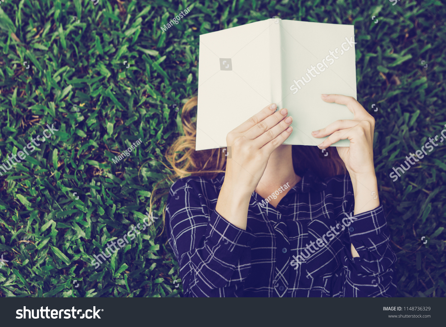 Closeup of young woman reading book, covering her face with it and lying on grass in park. Top view. #1148736329