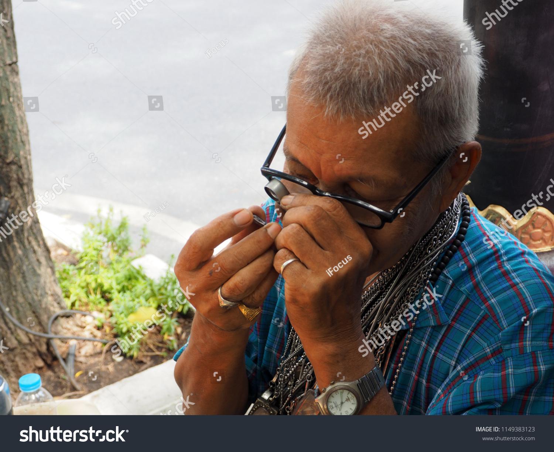 BANGKOK, THAILAND - AUGUST 4, 2018: A man uses a magnifier to check an amulet on August 4, 2018 in Bangkok, Thailand.