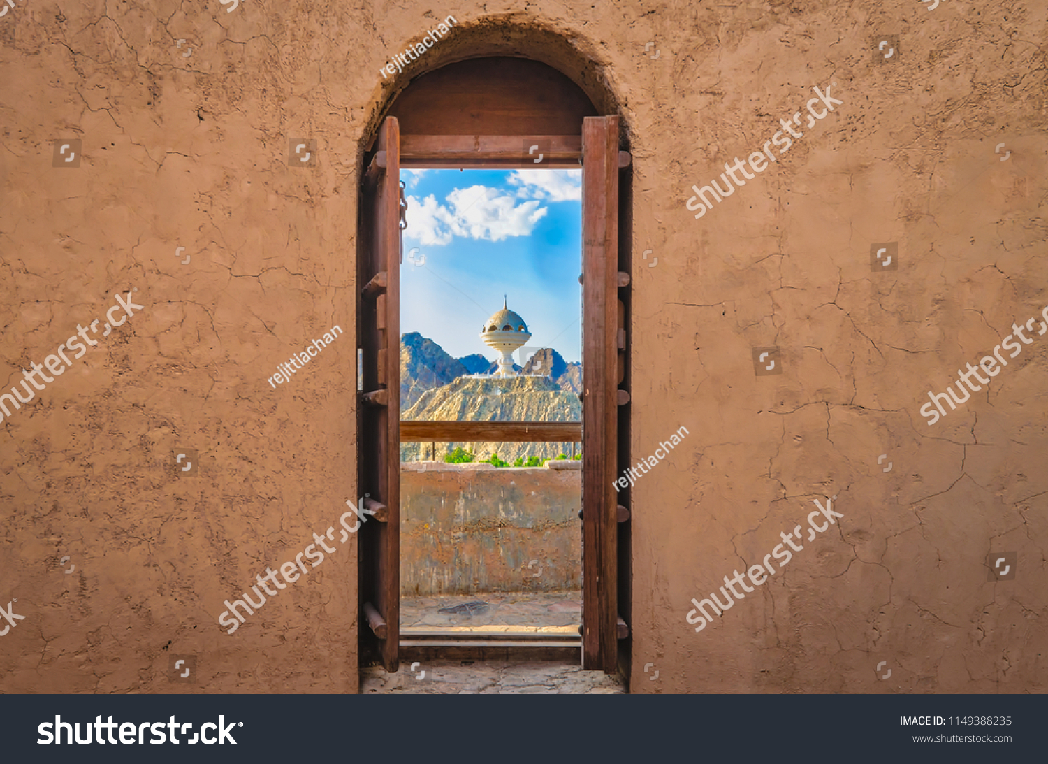 Narrow archway with old, heavy wooden doors opened to show the famous frankincense monument of Muscat, Oman.
