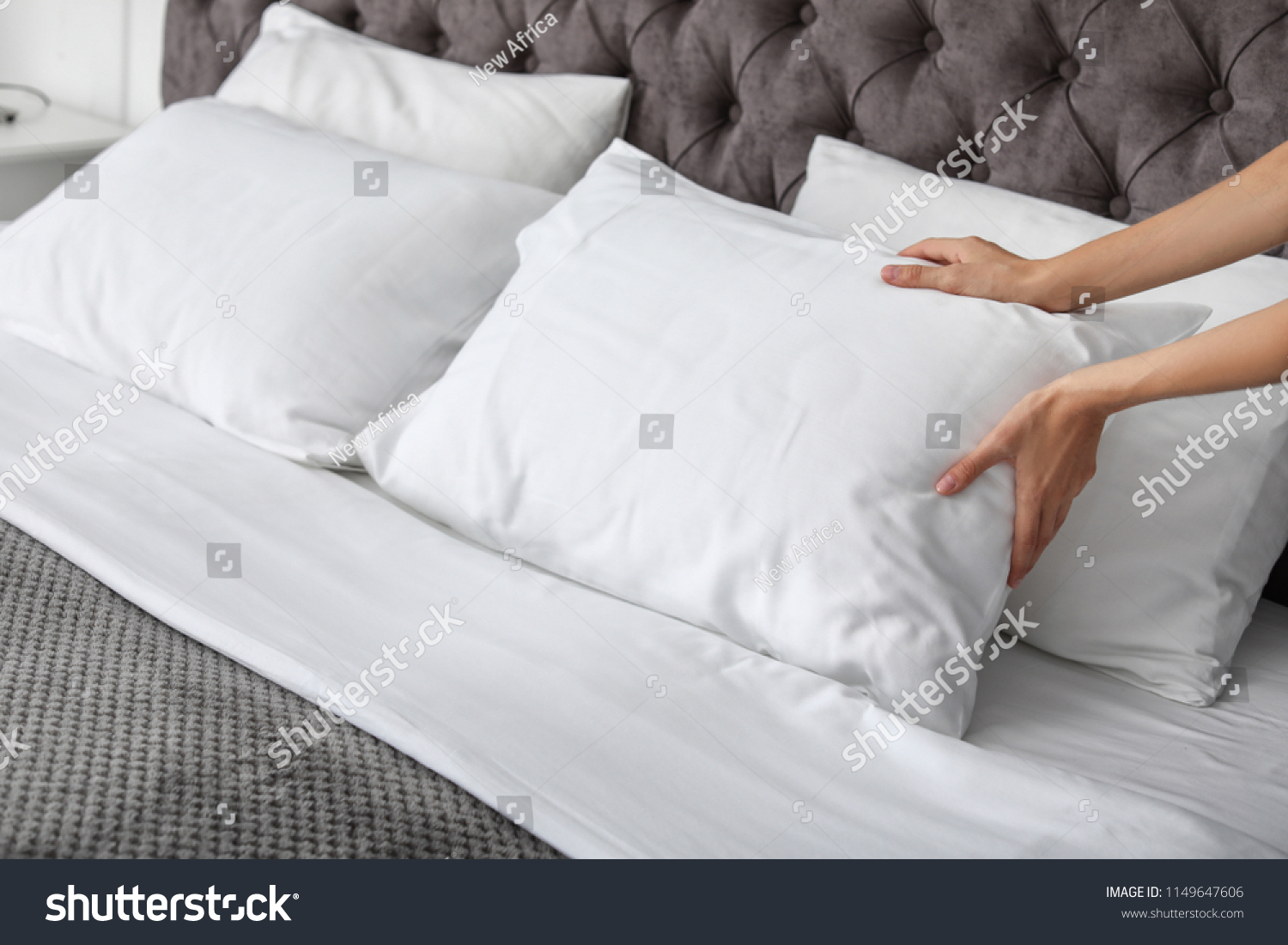 Young woman plumping white pillow on bed, closeup