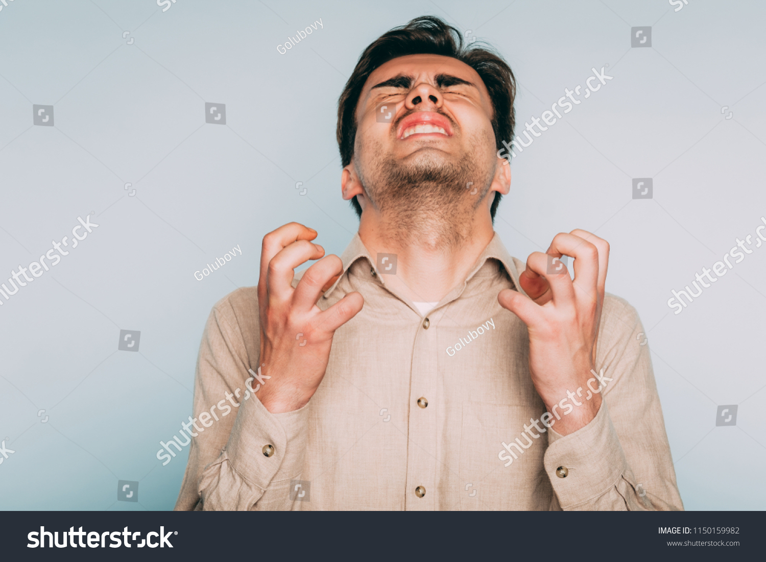 infuriated rage and anger. man went berserk with fury. portrait of a young brunet guy on light background. emotion facial expression. feelings and people reaction concept. #1150159982