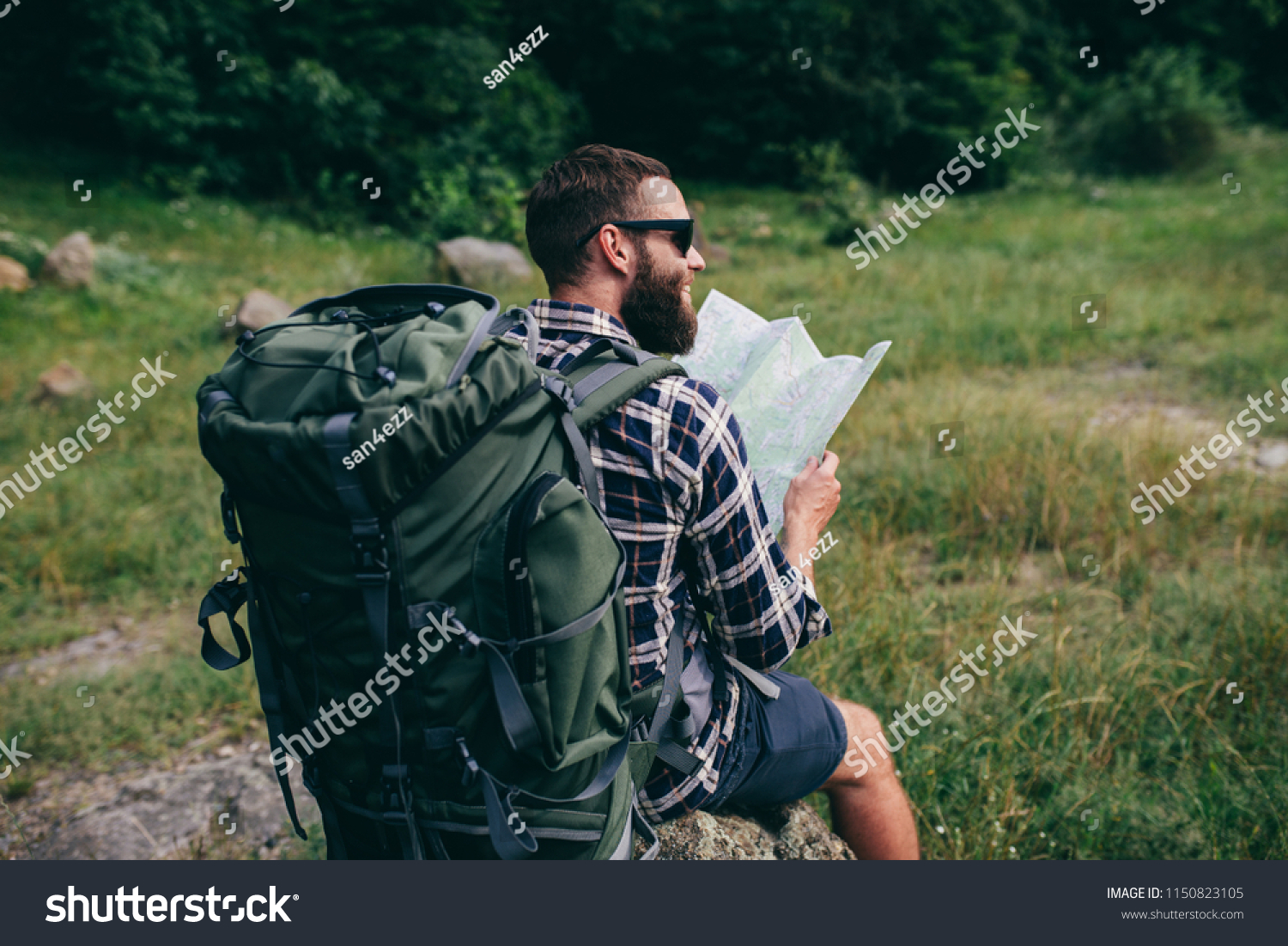 d8bb821c04aa bearded tourist in sunglasses with big traveling backpack and map moving up  on the mountain trail