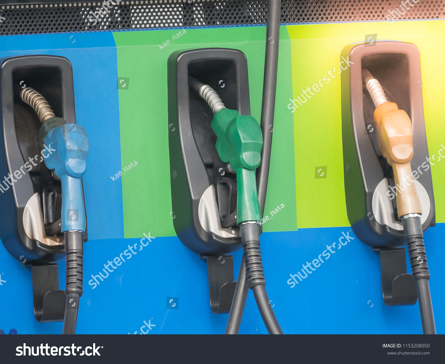 blue green orange fuel gasoline dispenser nozzles background at gas station #1153208050