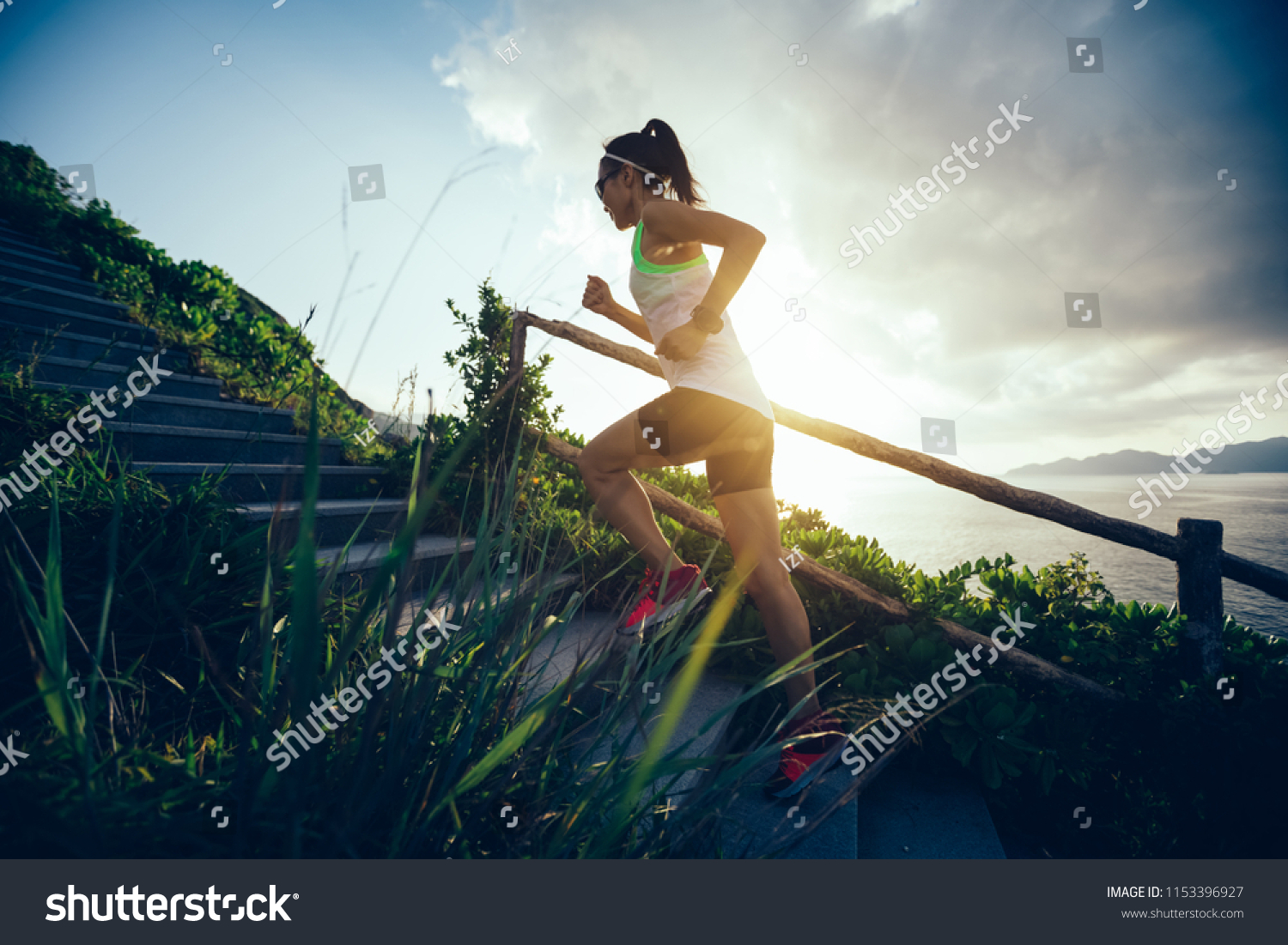 Determined woman running up on seaside mountain stairs #1153396927