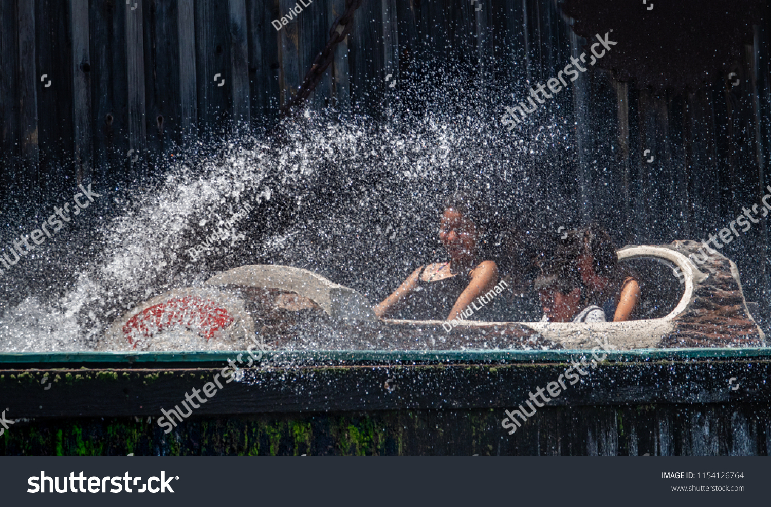 Santa Cruz, California - July 24, 2018: People are splashed and drenched with water, obscuring their faces, at the bottom of Logger's Revenge flume water ride  at Pacific Park on a hot summer day.