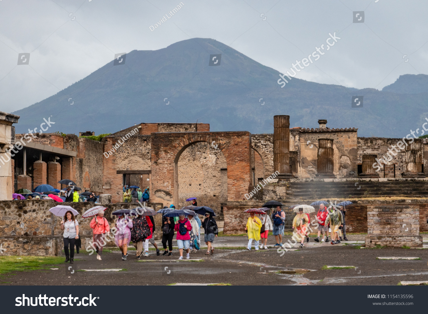 Campania, Italy - June 14, 2018: Tourists visit the archaeological ruins of Pompeii on a rainy day, wearing ponchos and carrying umbrellas.  The volcano Mount Vesuvius stands in the background.