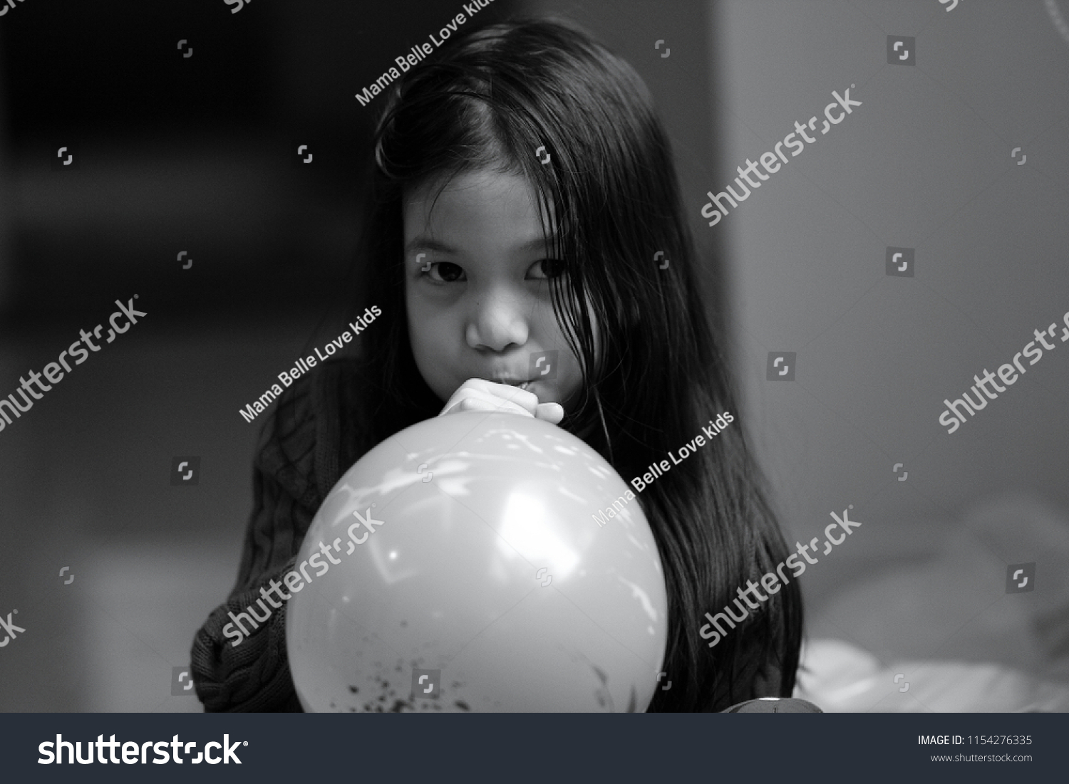 Black and white image of 6 years old Asian girl Blowing balloons.Girl look  happy