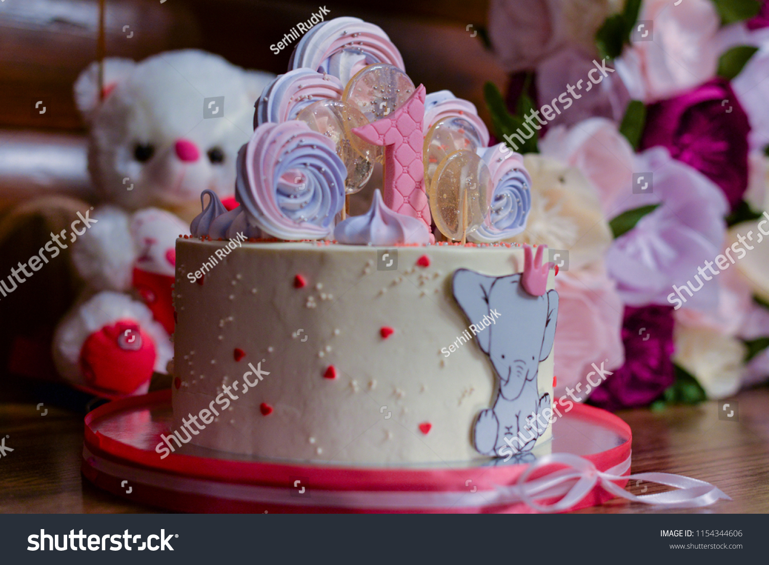 Cake Made From White Mastic With Candies For Birthday Against The Background Of Flowers