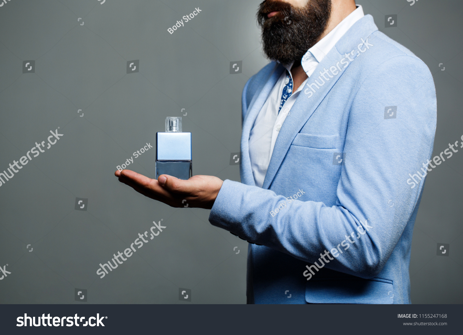 Male holding up bottle of perfume. Man perfume, fragrance. Perfume or cologne bottle and perfumery, cosmetics, scent cologne bottle, male holding cologne. Masculine perfume, bearded man in a suit.