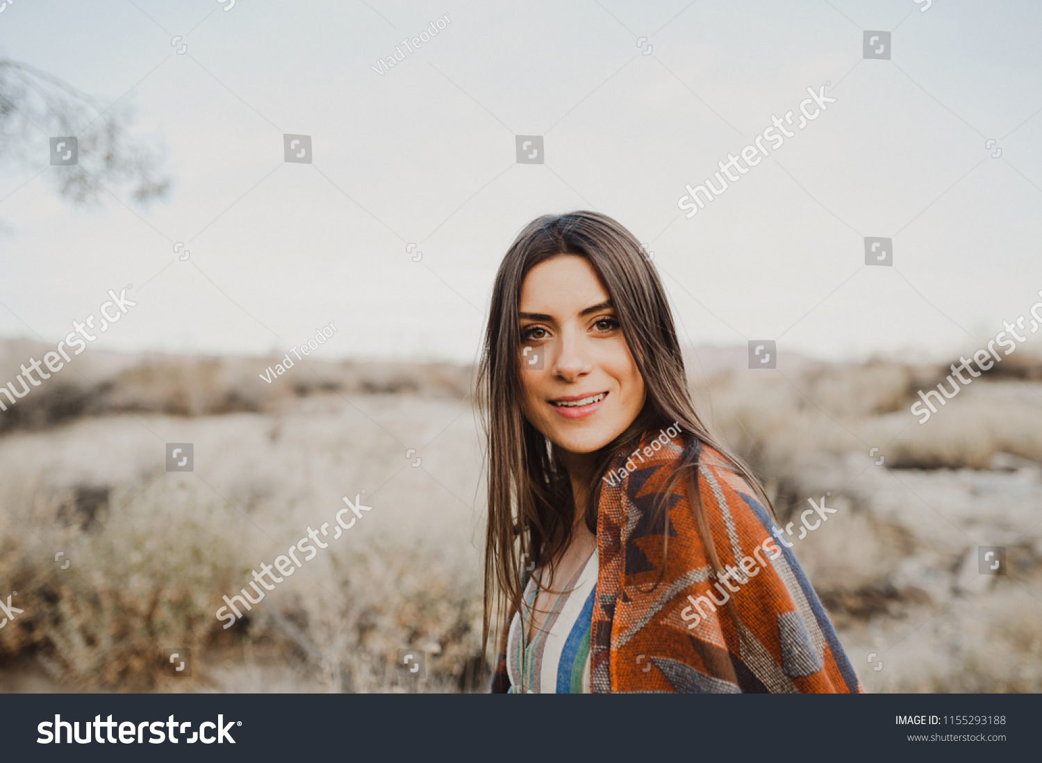 Smiling, beautiful hipster traveler girl in gypsy look and windy hair, in desert nature