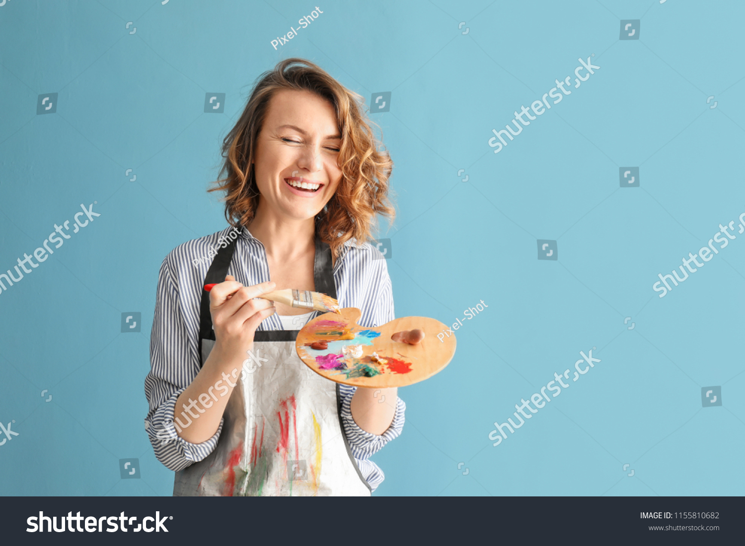 Female artist with brush and paint palette on color background #1155810682