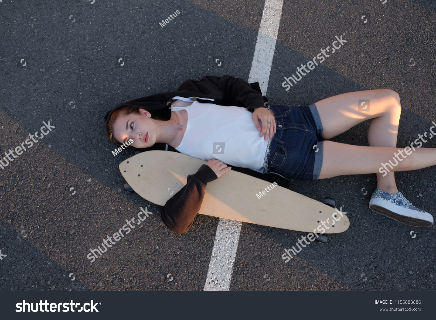 Street fashion  girl lying down with longboard on road surface in sunny day