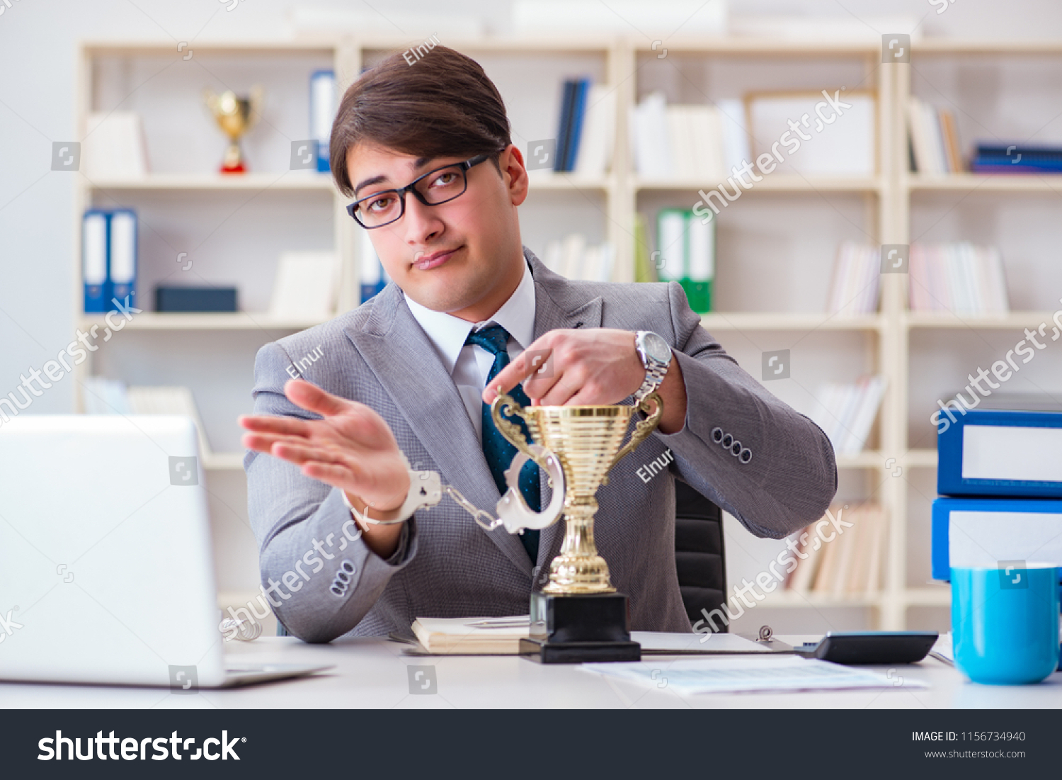 Businessman with golden cup in the office #1156734940