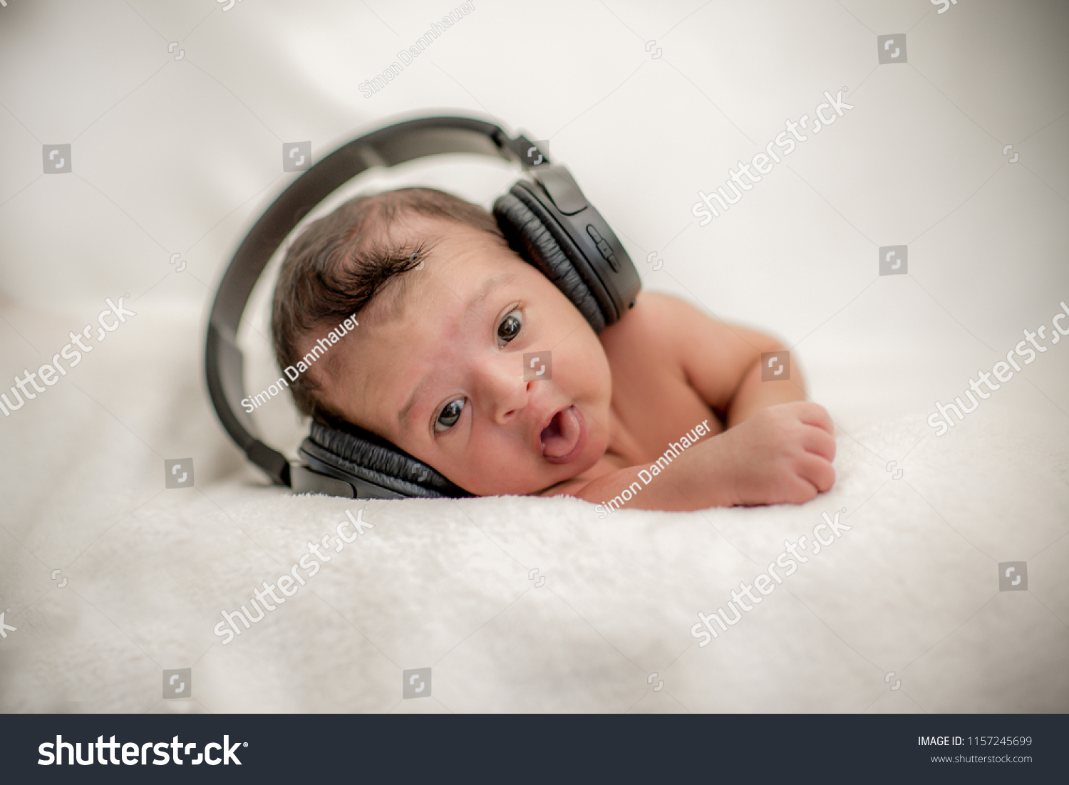 Cute newborn baby hearing music with headphones on a blanket happy family moments