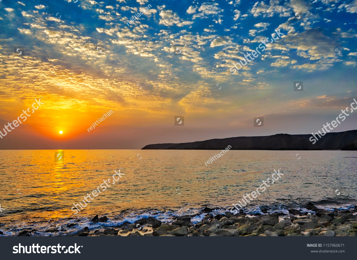 Beautiful Sunrise on the beach. Full view of the ocean, the waves, mountains and the sky.
