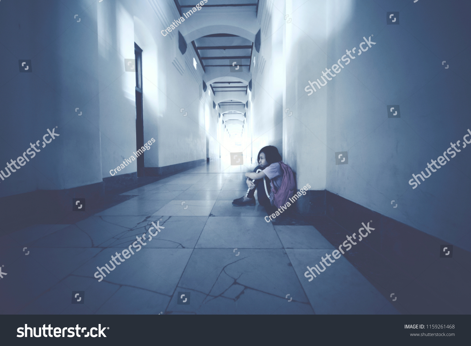 Picture of Asian schoolgirl looks depressed while sitting alone in the school corridor #1159261468