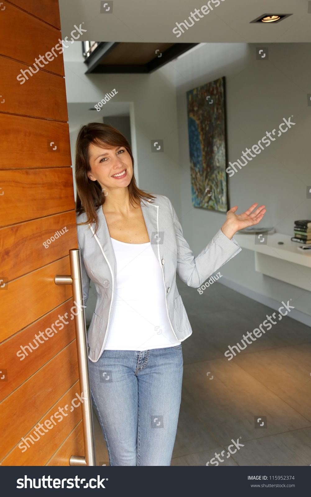 People Opening Doors : Woman opening her house door welcome stock photo