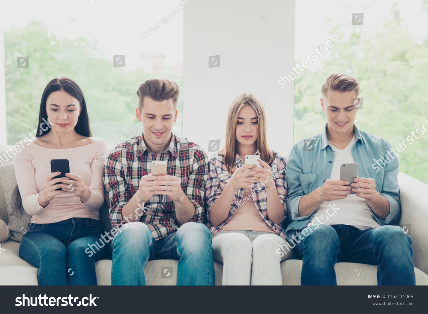 Four young people in jeans and shirts holding modern phones and smiling sitting at home on a white sofa in a bright room #1162115068