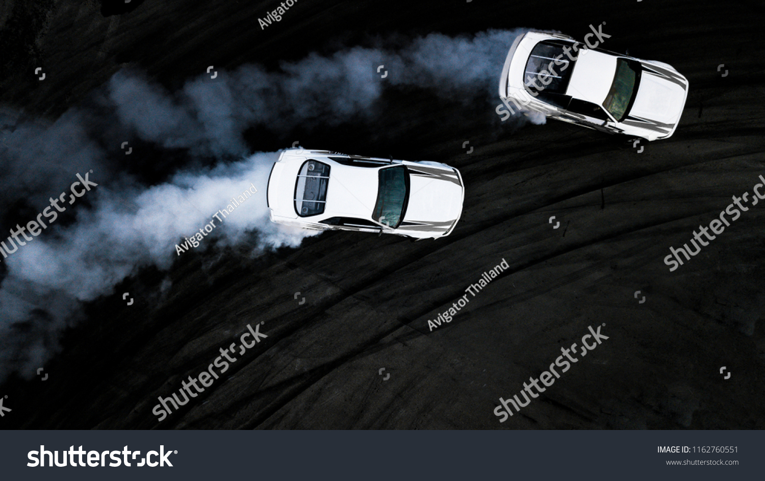 Two car drifting battle on asphalt street rad race track, Race car drift performance view from above, Car drifting, Automobile and automotive drift car with smoke from burning tire on speed track. #1162760551