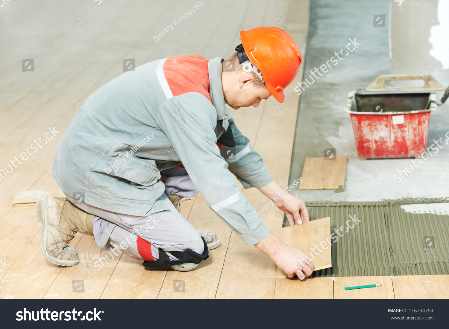 Industrial tiler builder worker installing floor stock photo industrial tiler builder worker installing floor tile at repair renovation work dailygadgetfo Gallery
