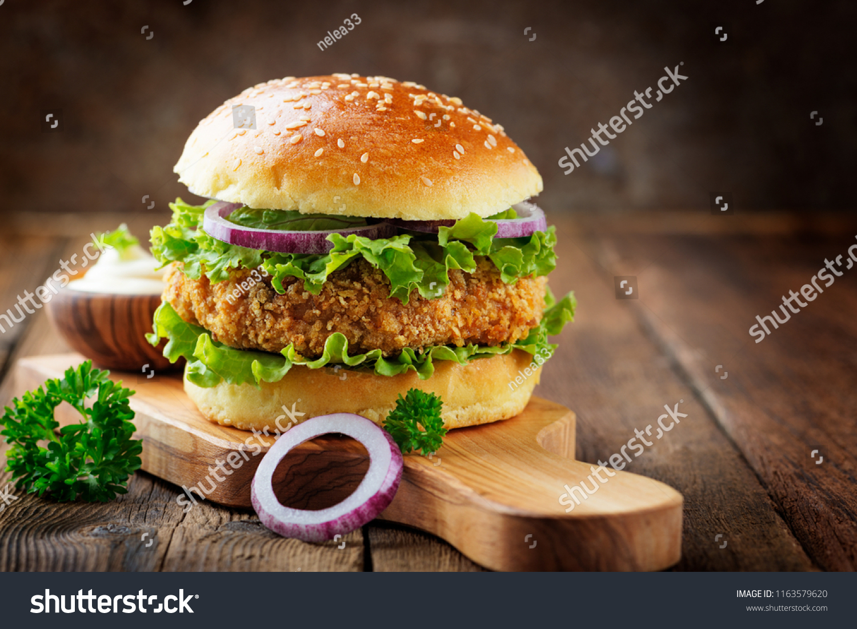 Fresh tasty chicken burger on wood table. #1163579620