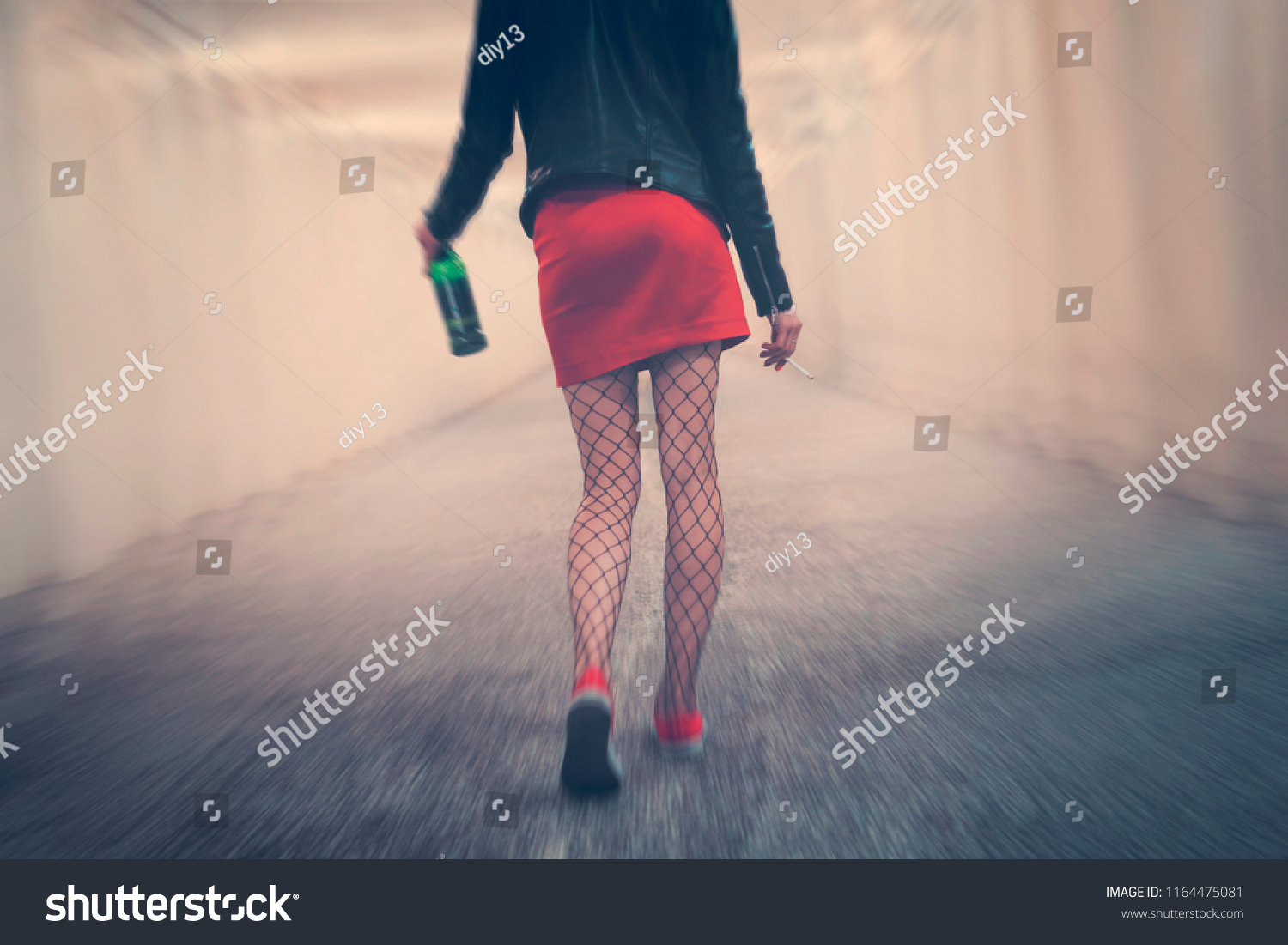 drunk woman with cigarette and bottle goes into distance along corridor  stumbling and falling. Young