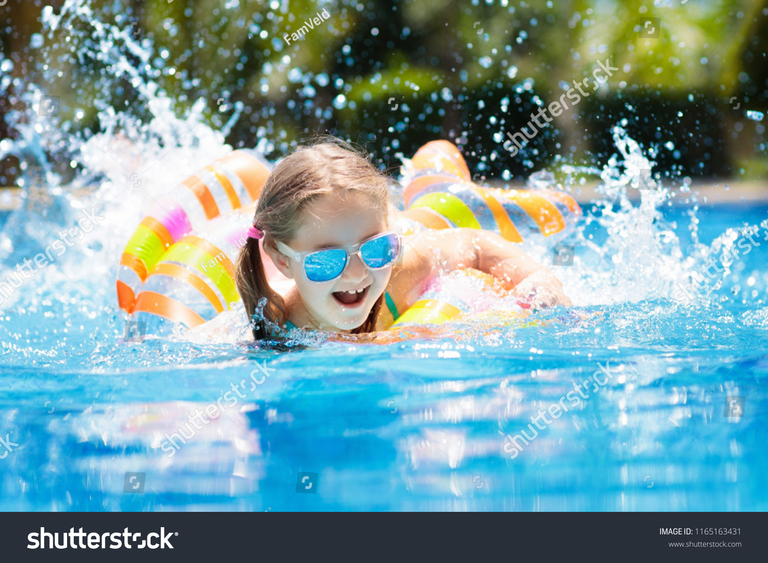 65363118188 Child with inflatable toy ring float in swimming pool. Little girl learning  to swim and