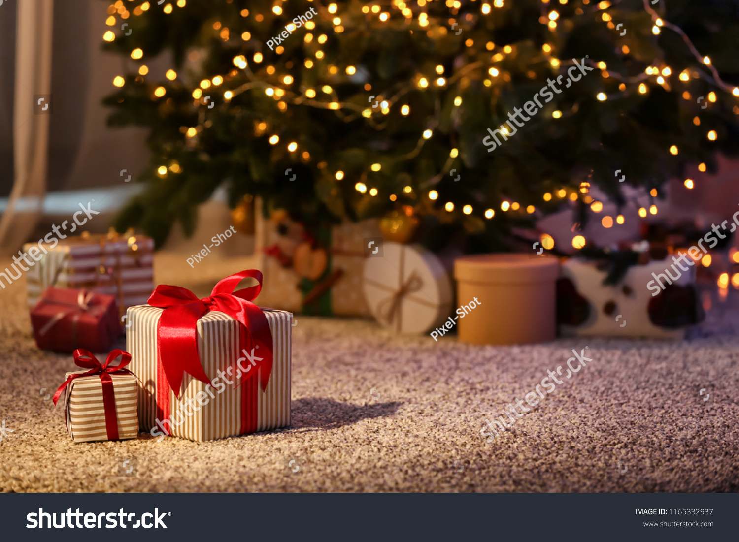Beautiful Christmas gift boxes on floor near fir tree in room #1165332937