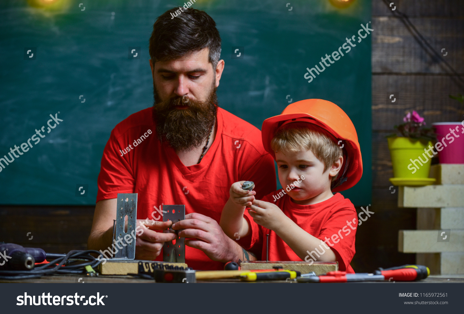 Father with beard and little son in classroom teaching to use tools