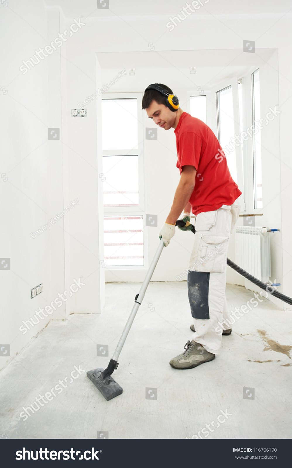 Worker Cleaning Floor With Vacuum Cleaner From Industrial