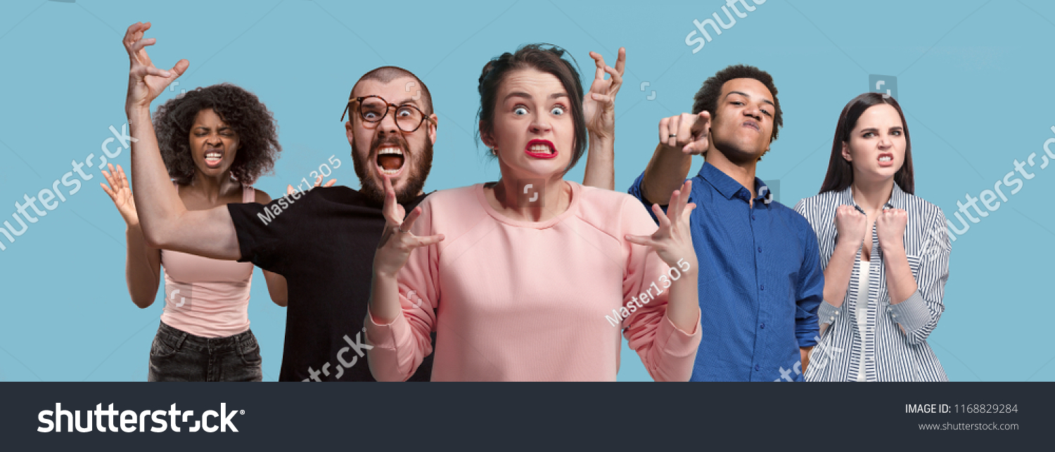 What is it. The male and female portrait isolated on blue studio backgroud. Anger. Young, emotional, angry, scared people looking at camera. Human emotions, facial expression concept. Trendy colors #1168829284