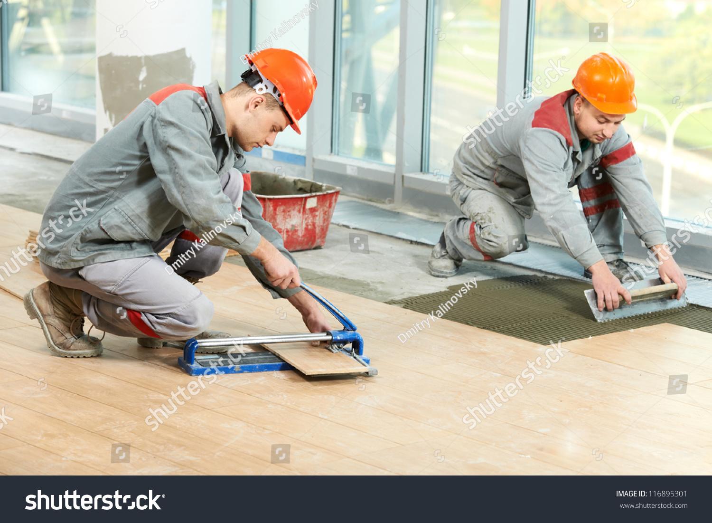 Two industrial tiler builder worker installing stock photo two industrial tiler builder worker installing floor tile at repair renovation work dailygadgetfo Image collections