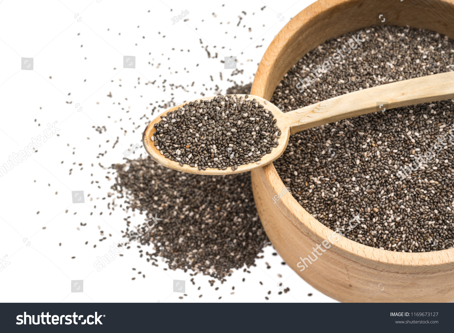 Close up of chia seeds in wooden spoon on top of a wooden bowl with some spread on the blurred white background seen obliquely from above #1169673127