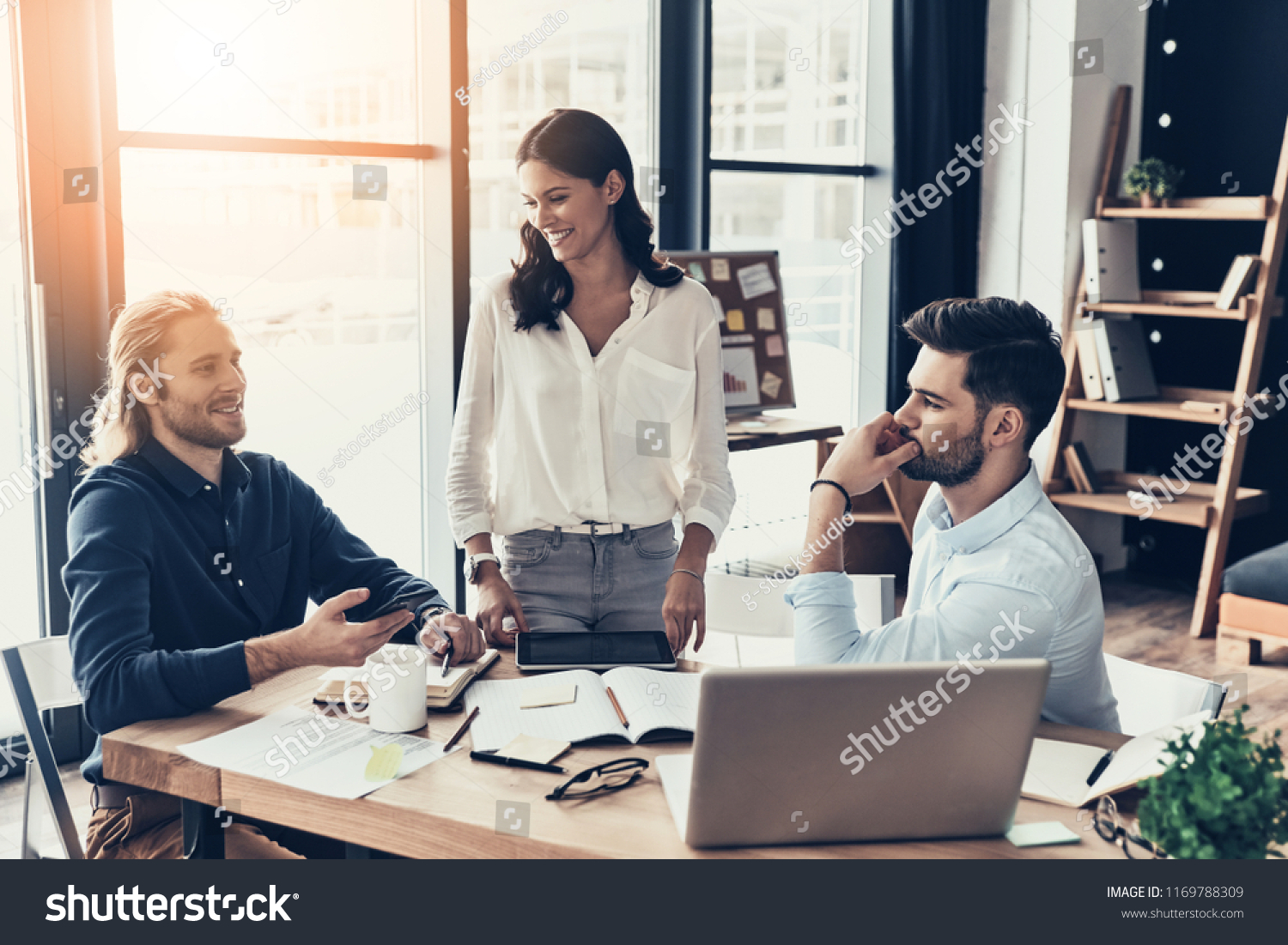 e1a0fa33ca8 Young coworkers. Young modern colleagues in smart casual wear working  together and smiling while spending