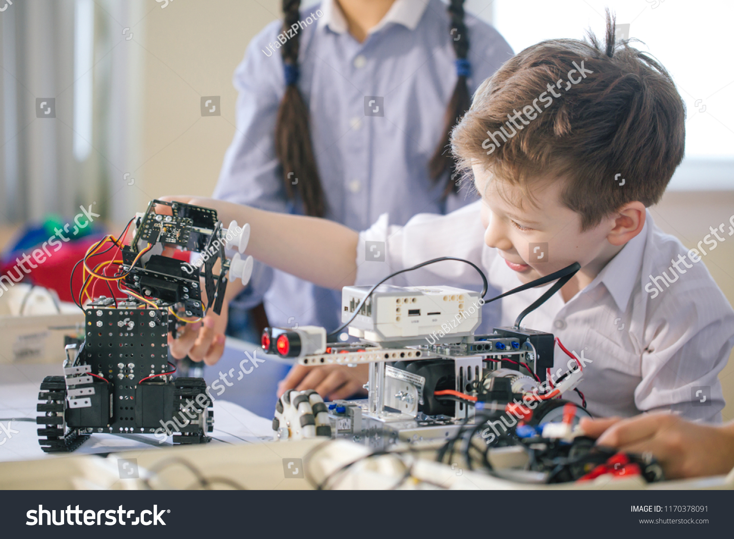 Fair haired cheerful little boy making a robot from metal parts and microcircuits, his sister helps him, close up. Happy emotion and enjoyment. #1170378091