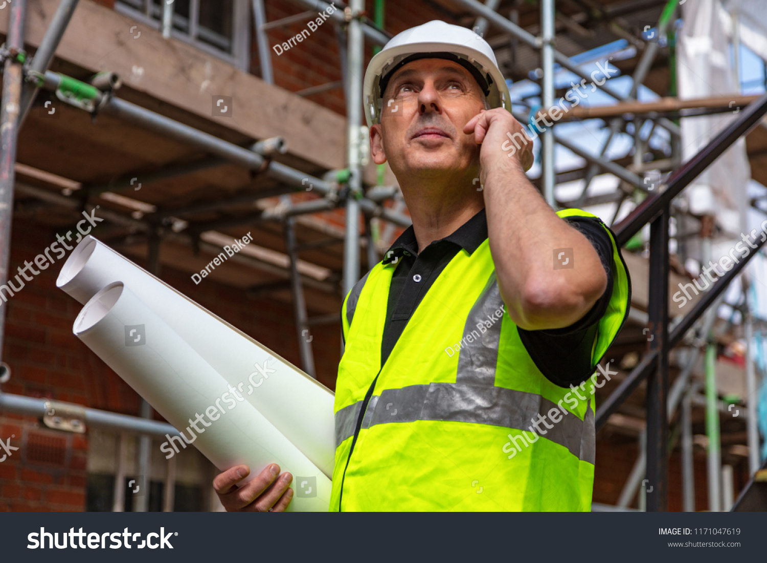 Male builder foreman, worker or architect on construction site holding building plans and talking on his cell phone #1171047619