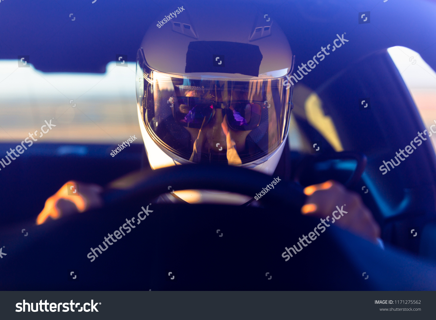 A Helmeted Race Car Driver At The Wheel #1171275562