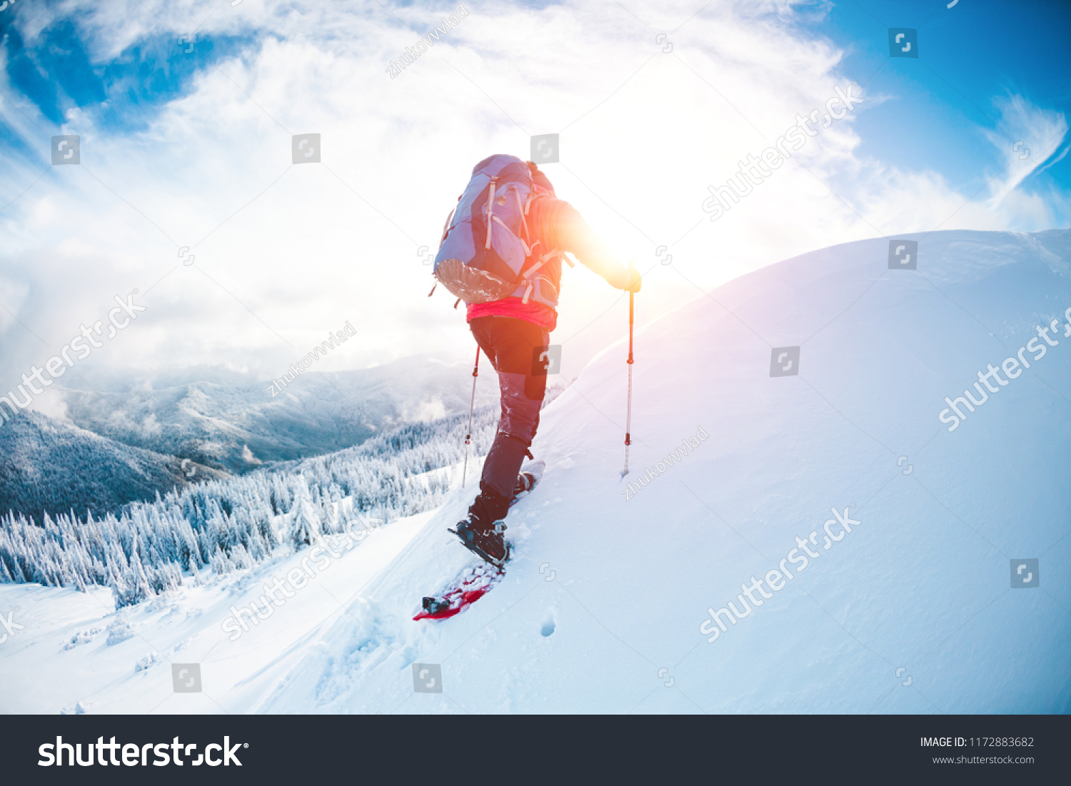 A man in snowshoes in the mountains in the winter. A climber with trekking sticks walks through the snow. Winter ascent. Beautiful sky with clouds. #1172883682