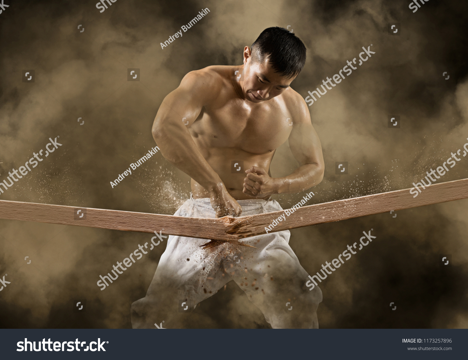 Determined karate man breaking with hand wooden board #1173257896