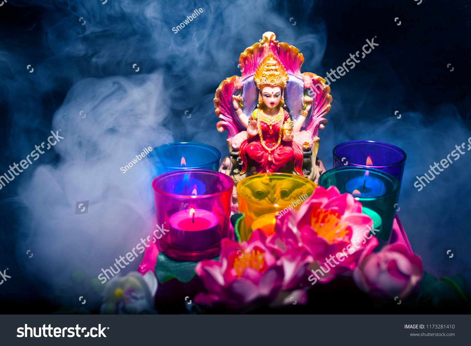 Hindu goddess lakshmi statue smoke candles stock photo edit now statue with a smoke candles and lotus flowers on a black izmirmasajfo