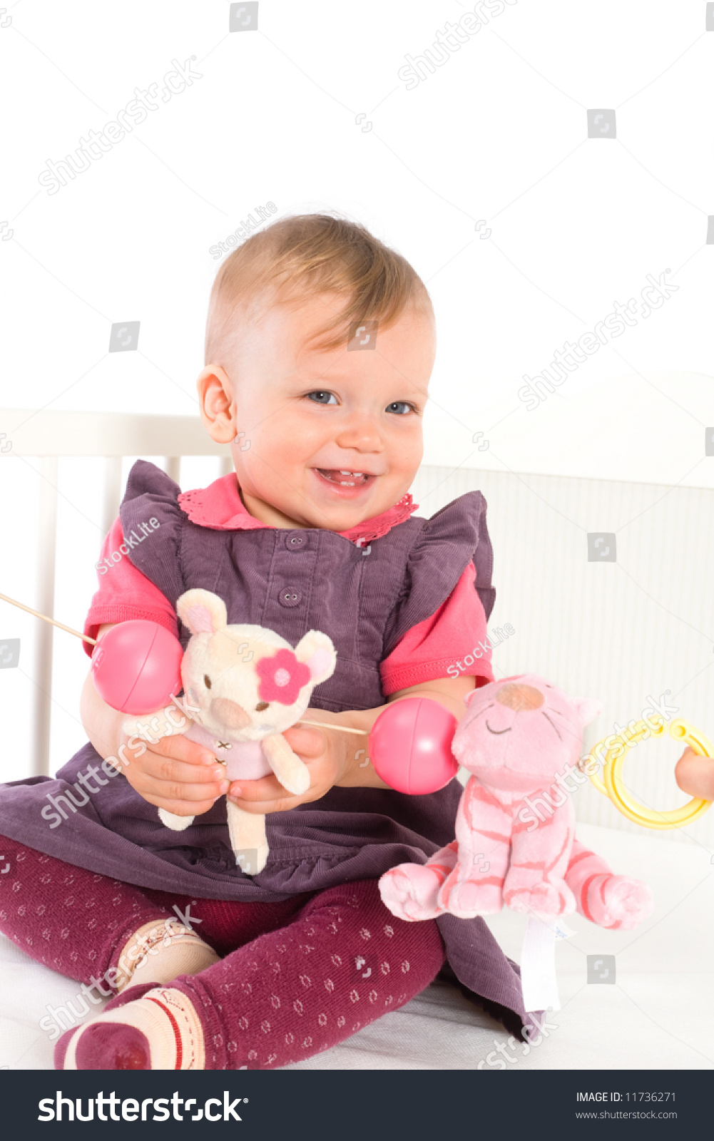 Cute Baby Girl (1 Year Old) Sitting On Crib, Holding Soft ...