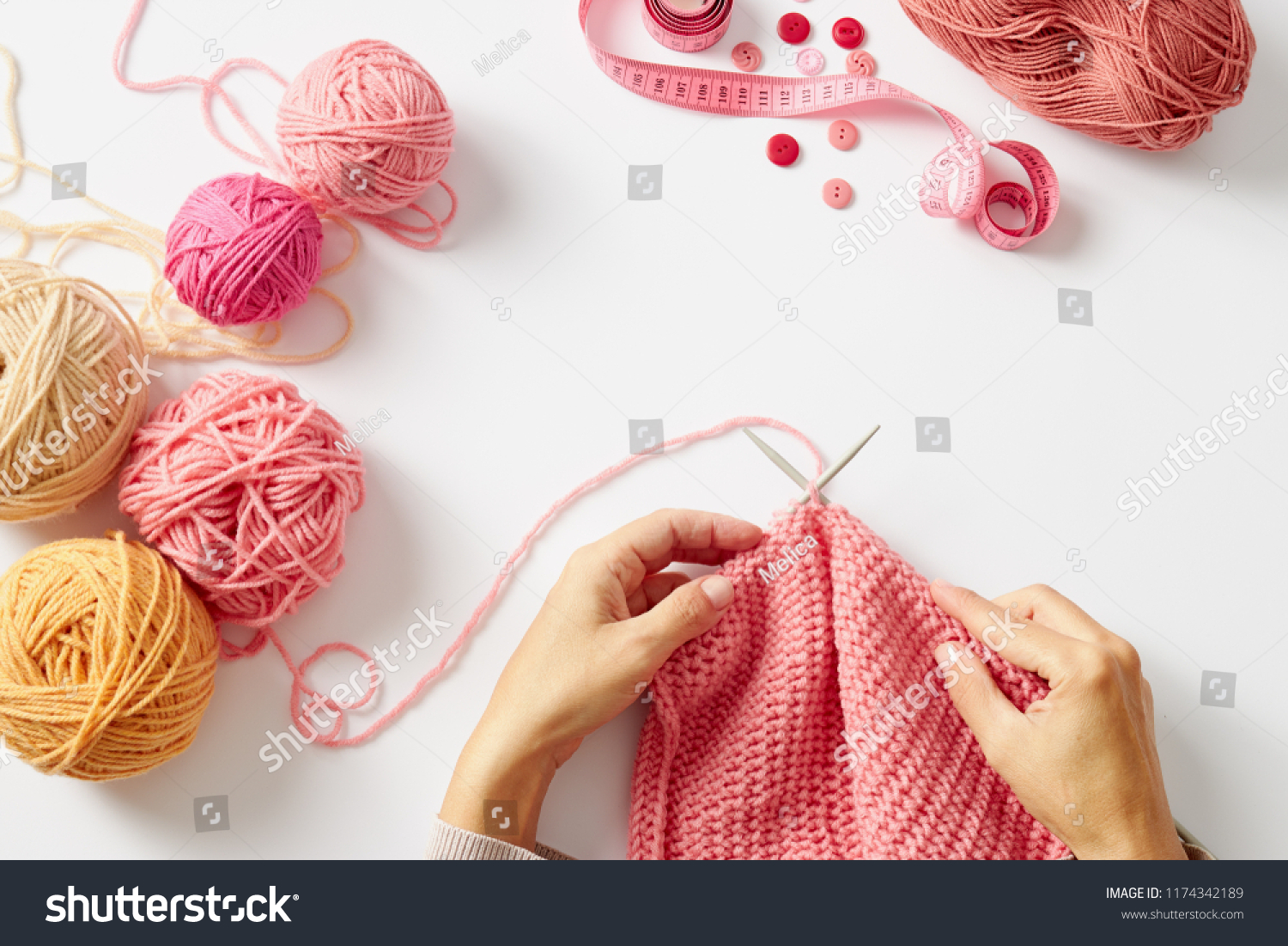 Female hands knitting with pink wool, on a white background, top view