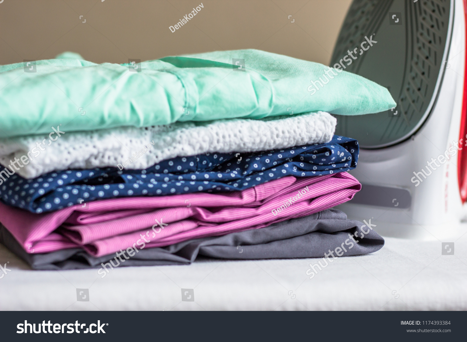 Iron on the ironing board and non-ironed clothes #1174393384