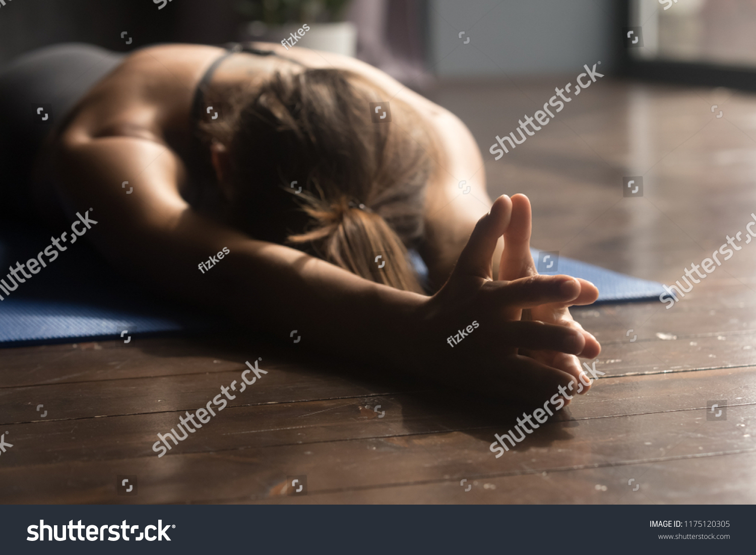 Young sporty attractive woman practicing yoga, doing breathing exercise, relaxation pose, working out, wearing sportswear, indoor close up, yoga studio