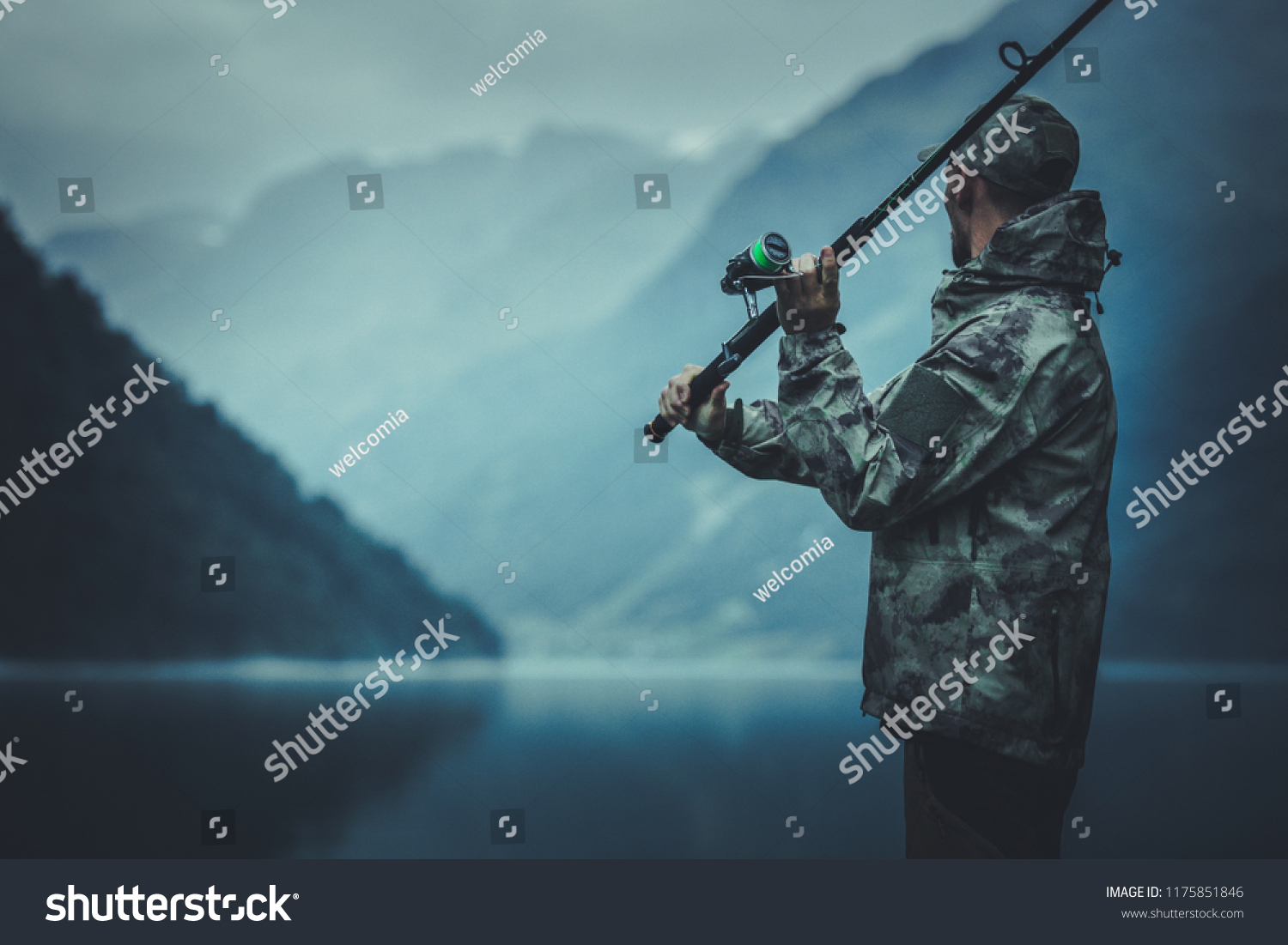 Evening Fly Fishing Time. Caucasian Fisherman with Fishing Rod on the Glacial Lake Shore. #1175851846
