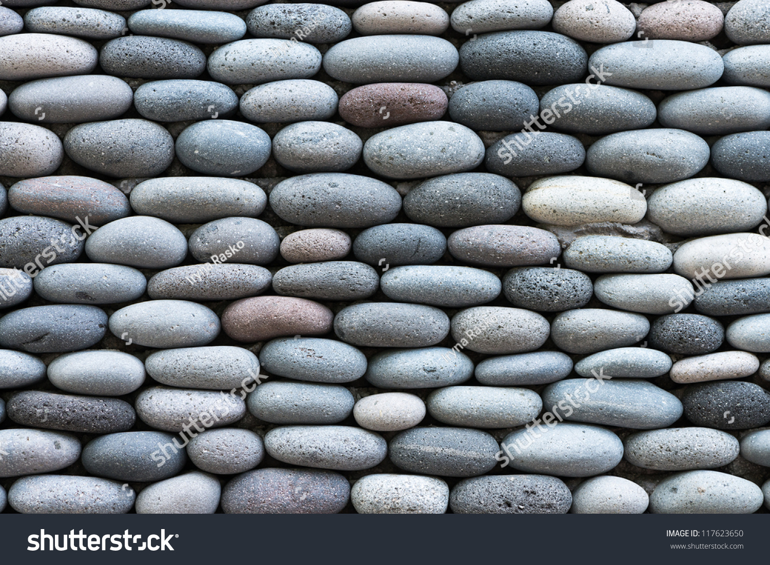 Smooth shaped white stones surface texture background stock photo - Peddle Stone Wall Texture Background