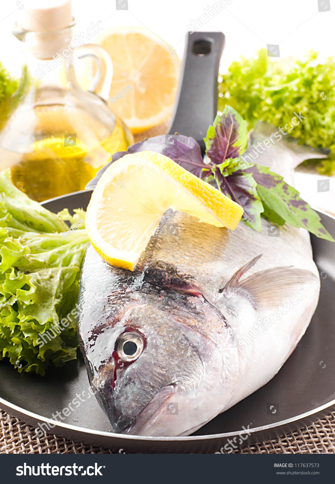 Fresh fish dorado on frying pan stock photo 117637573 for Frying fish in olive oil