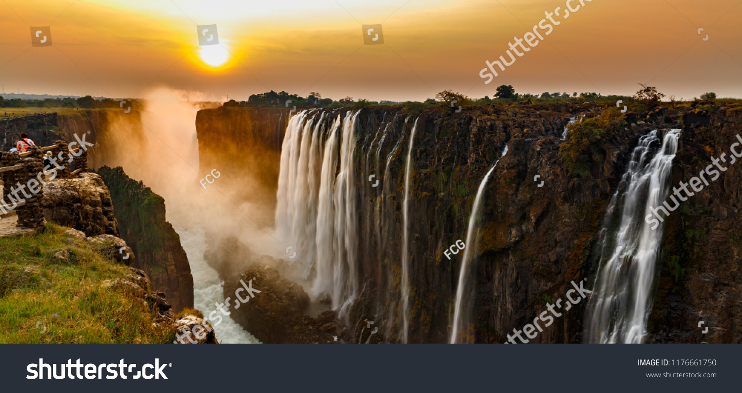 Wide panorama of victoria falls at sunset with orange sun in the sky and tourist in viewpoint #1176661750